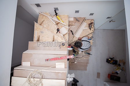carpenter installing wooden stairs