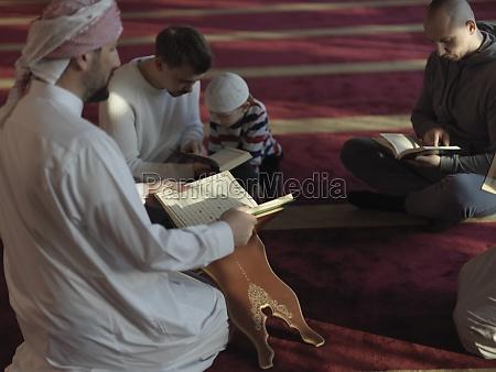 muslim people in mosque reading quran