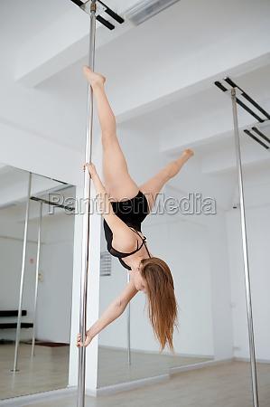 slim woman on pole dancing training