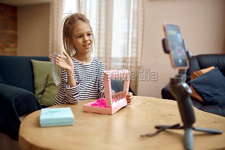 little girl recording blog on phone