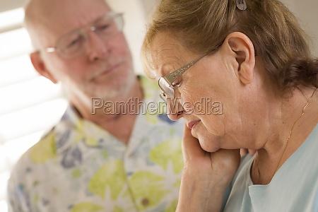 senior adult male consoles sad senior