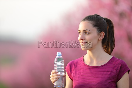 satisfied runner looking away holding water