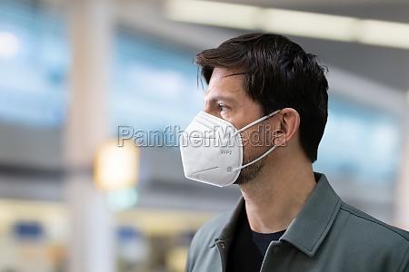 plane passenger in airport wearing facemask
