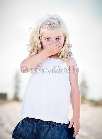 adorable blue eyed girl covering her