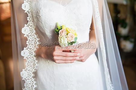bride holding wedding boutonniere in hands