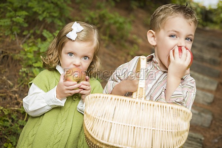 adorable children eating red apples outside