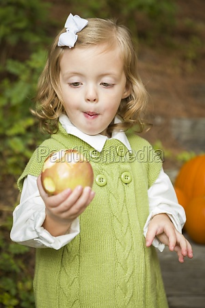 adorable child girl eating red apple