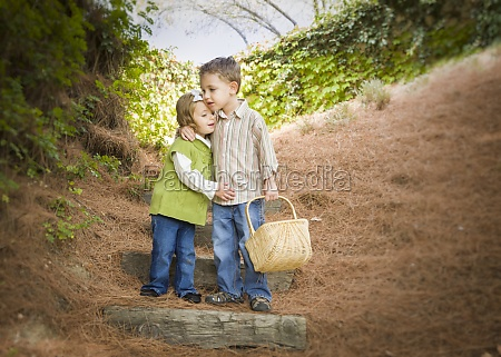 two children with basket hugging outside