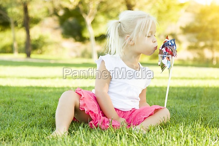 little girl in grass blowing on