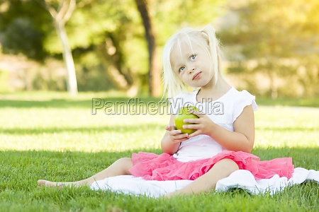 little girl in grass eating healthy