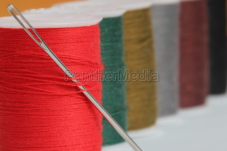 red cotton reel with needle with
