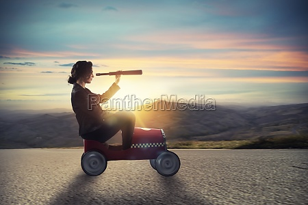 businesswoman with telescope on a car