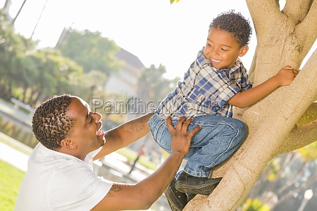 happy mixed race father helping son