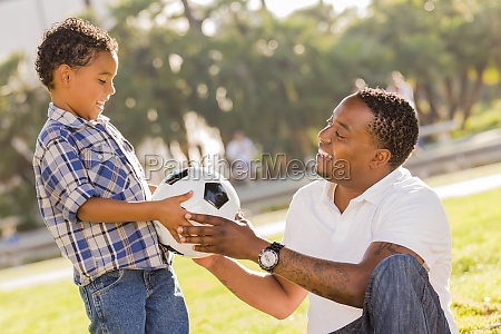 father hands new soccer ball to