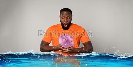 man holds a piggy bank that