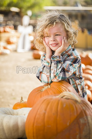 little boy smiles while leaning on