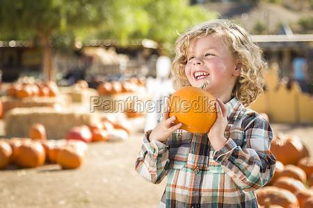 little boy holding his pumpkin at