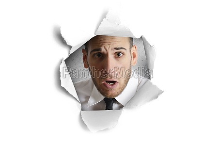 man looking through a paper hole