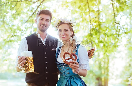 bavarian couple in tracht toasting with