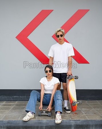 asian couple resting after skateboarding a