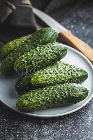fresh green cucumbers on black kitchen