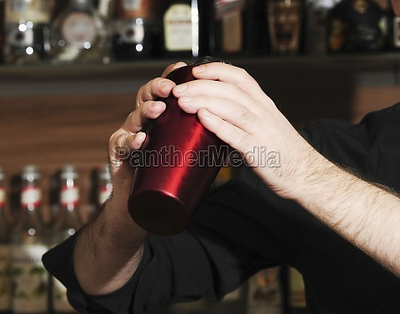 barkeeper mixing drinks together in a
