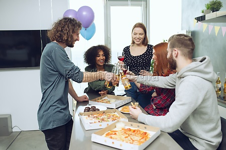 young friends eat pizza and drink