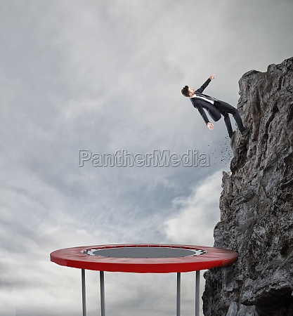 businessman jumping on a trampoline to