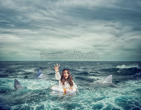 businesswoman with lifebelt surrounded by sharks