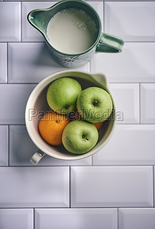 apples and oranges in ceramic bowl