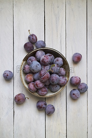 a dish of ripe plums against