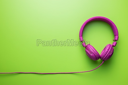 pink wired stereo headphones on green
