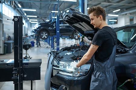 male mechanic adjusts the headlights car
