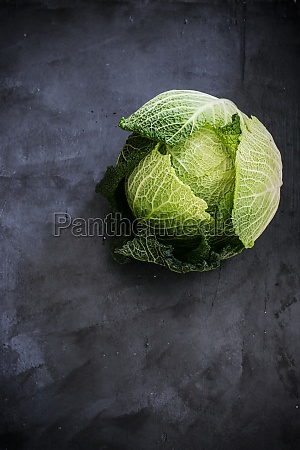 whole savoy cabbage on a dark