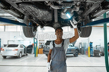 male mechanic checks car suspension auto