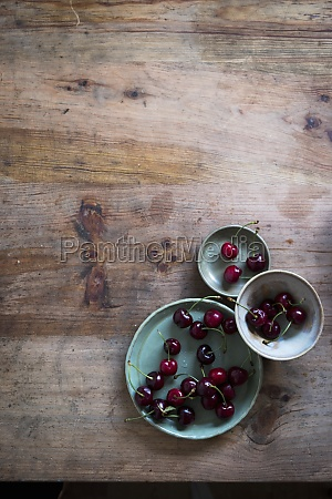 cherries on three green plates at