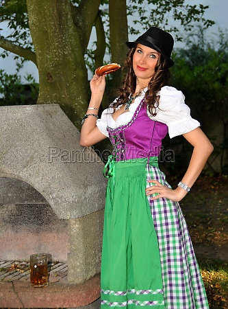 dirndl girl beside a stone grill