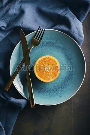 fresh orange in a teal plate