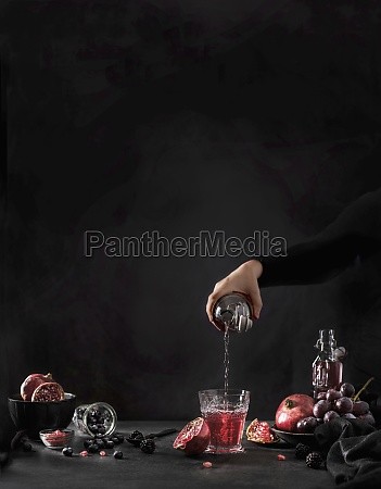 hand pouring pomegranate juice from bottle