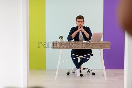 smiling young man freelancer using laptop