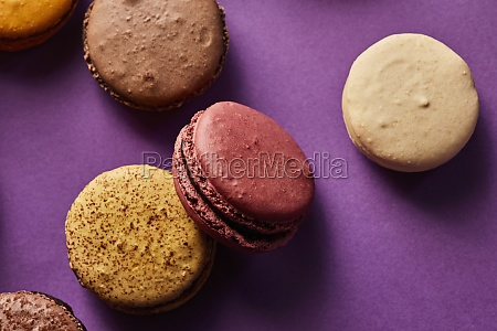 assortment of colorful macarons on purple