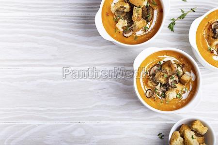 three white ceramic bowls with pumpkin
