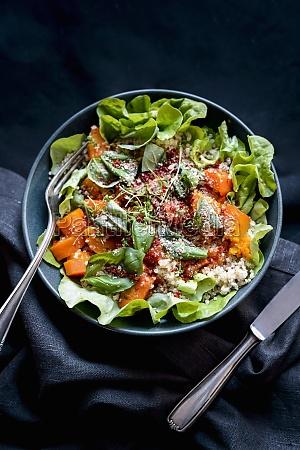 a salad bowl with lettuce pumpkin