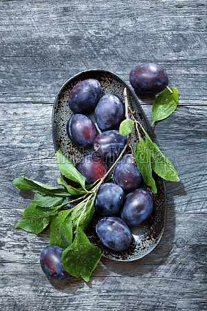 plums with leaves in a bowl