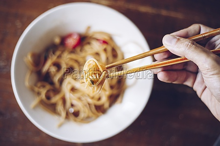 person holding shrimp by wooden chopsticks