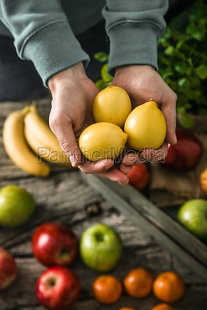 farmer holding harvested fruit and vegetables