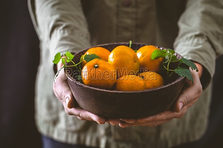hands holding a bowl of tangerines