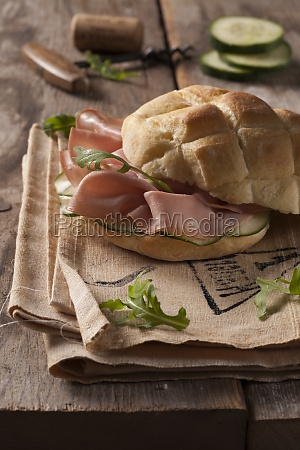 a bread roll with mortadella cucumber