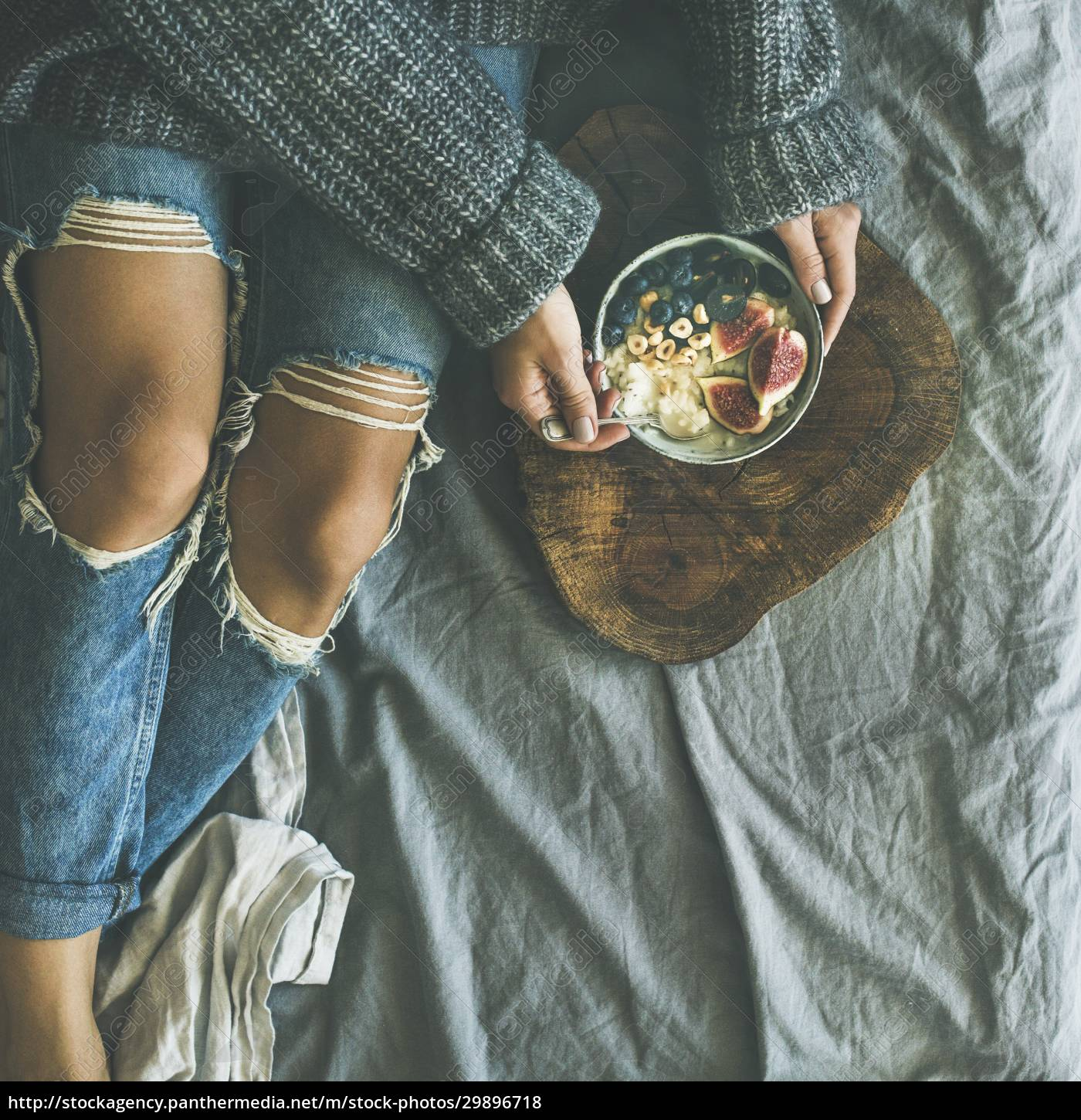 woman, in, sweater, and, jeans, eating - 29896718