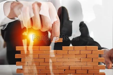 businessman puts a brick to build